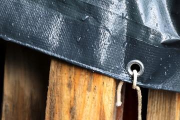 Plastic cloth with water drops. Waterproof surface. Woody palette under grey tarpaulin. Fototapete