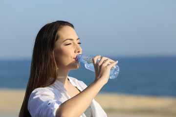 Lady drinking water from a bottle on the beach