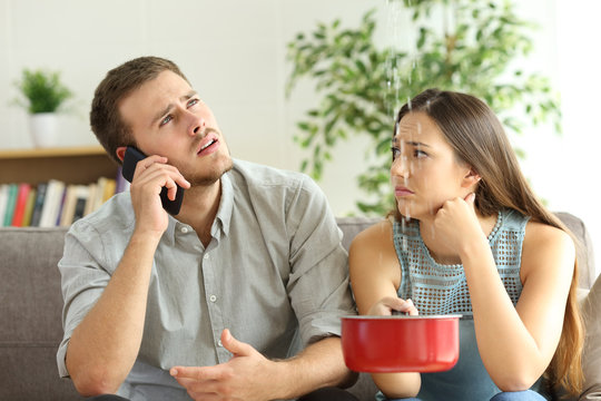 Couple callling to insurance for home leaks