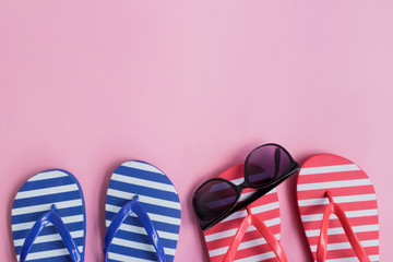 Flip flops and sunglasses on a pink background