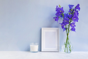 Mockup with a white frame and summer blue flowers in a vase