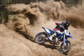 Fotobehang Motorsport Motocross rider creates a large cloud of dust and debris