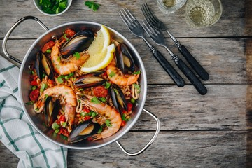 Spanish seafood paella with mussels, shrimps and chorizo sausages in traditional pan on wooden background.