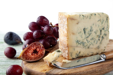 Stilton on a cheese board with red grapes, fig and cheese knife