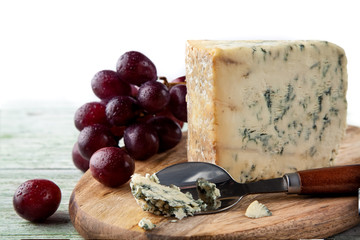 Stilton on a cheese board with red grapes and cheese spoon