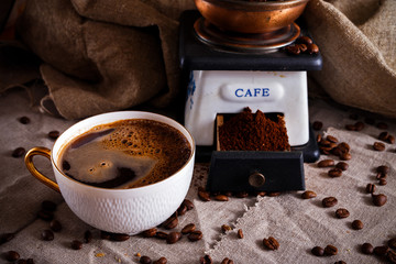 A cup of black coffee with a bun, coffee beans and pieces of sugar scattered on a table covered with sackcloth.