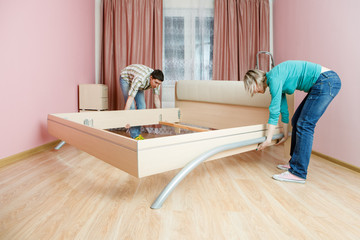 Photo of man and woman rearranging bed