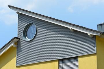 Seitliche Verkleidung des oberen Stockwerks mit verzinktem und RundfensterWellblech er Stehfalz-Metall-Dachabschluss, Zinkblech-Dachrinne und Schneefang an einem Wohnhausdach