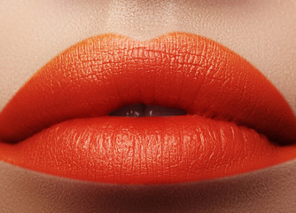 Close-up macro shot of female mouth. Sexy Glamour red lips Makeup with sensuality gesture. Orange colour