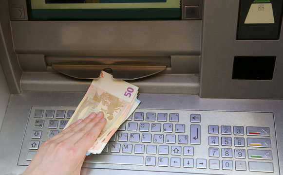 withdraws money euro banknotes from an ATM of a European bank
