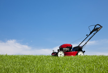 Lawn mower in the green grass against a blue sky in the summer