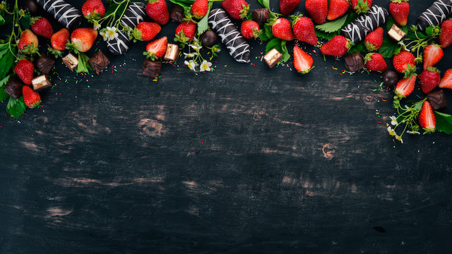Strawberry with chocolate and candy. On a black wooden background. Top view. Copy space.