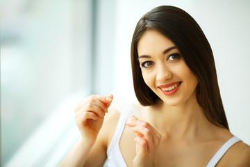 Teeth Whitening. Beautiful Smiling Woman Holding Whitening Strip. High Resolution Image