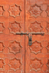 The wooden doors of dark orange color executed in the form of patterns from 8-pointed stars, closed on the lock.