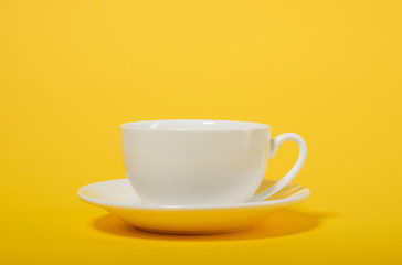 one simple coffee cup on yellow color background, closeup photo