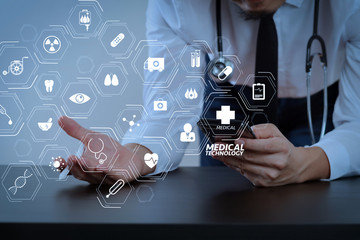 close up of smart medical doctor working with smart phone and stethoscope on dark wooden desk