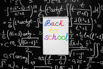 "Back to school background with title ""Back to school"" written on the white page of notebook  on the chalkboard with math formulas written by chalk on the blackboard"