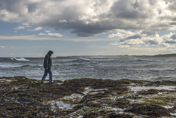 Lonely man walking on rocky shore in stormy weather