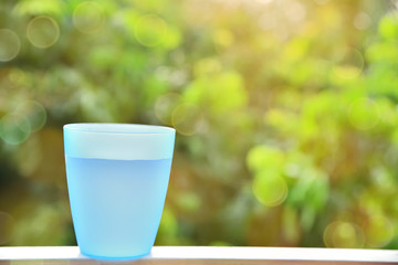 Blue plastic cup with water inside and blurred bokeh background