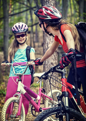 Bicyclist child ride on bicycle path in city. Children go down stairs in park. Mother with daughter have active leisure on fresh air outdoor. Tone image. Children travel unaccompanied.