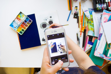 Woman hand holding phone taking photo of painting flat lay with brush, pencils and paints.
