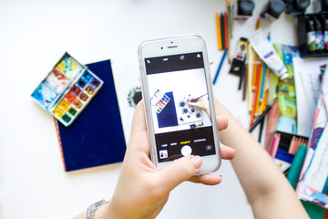hand holding phone taking photo of Flat lay artist space