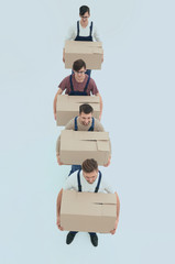 Young movers holding boxes standing in a row, isolated on white