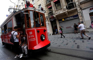 A vintage tram, with a closed shop in the background, runs along the main shopping and pedestrian street of Istiklal in central Istanbul