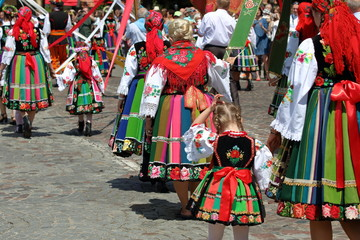 Kobieta ubrana w tradycyjny łowicki strój, od pasa w dół, stoi na słonecznej ulicy, kolorowa pasiasta sódnica z hafttowanymi kwiatami, biała koronkowa koszula, czarne  trzewiki