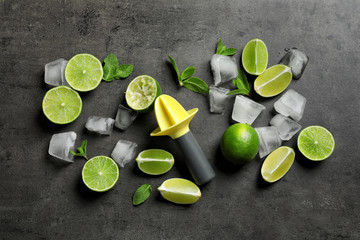 Flat lay composition with lime, mint and juicer on grey background. Refreshing beverage ingredients