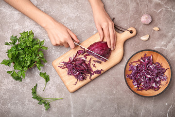 Woman cutting red cabbage on wooden board, top view