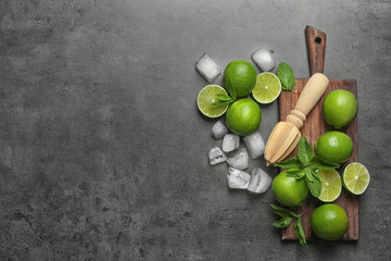 Flat lay composition with ripe limes, ice cubes and juicer on grey background. Refreshing beverage recipe
