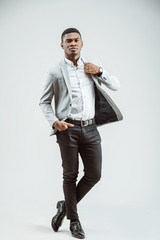 Full length portrait of attractive young African American business man in classic outfit posing in the studio. White background