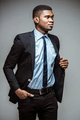 Handsome young African American business man in stylish classic black suit posing in fashion position isolated on grey background. Studio shot
