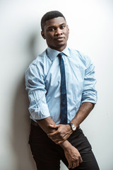 Portrait of attractive young African American Business man wearing blue shirt, black trousers posing against white background indoors in thr studio