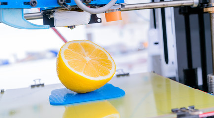 Ripe slice of yellow lemon citrus fruit . 3d printer of the device during the processe.