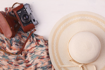 Woman clothing and accessories placed on a wooden background.