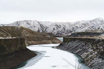 Frozen river with snow mountains in canyon