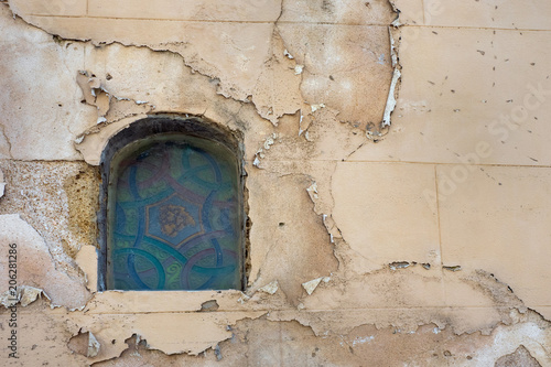 A Small Arched Window With A Vintage Colored Glass On The