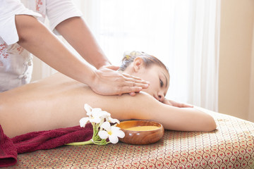Woman is having shoulder massage in Thai style