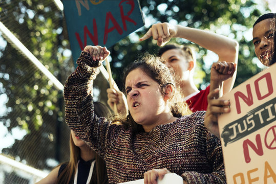 Closeup of angry teen girl protesting demonstration holding posters antiwar justice peace concept
