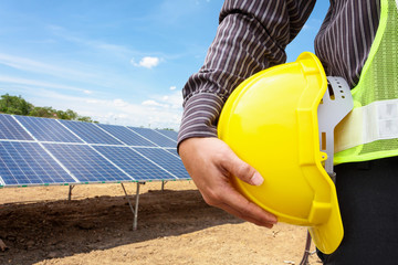 Young business man engineer hold yellow helmet at solar panel power plant construction site background
