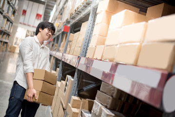 Young Asian man carrying cardboard boxes near product shelf in warehouse, shopping warehousing or working pick and packing concepts