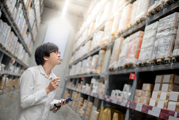 Young Asian man checking the shopping list and looking for product in warehouse wholesale, shopping warehousing concept