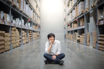 Young Asian man sitting in warehouse choosing what to buy, shopping warehousing concept
