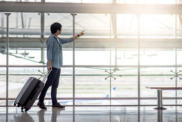 Young Asian man walking with suitcase luggage in the airport terminal pointing the plane taking off, travel lifestyle