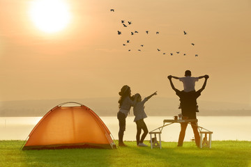 Happy family camping near the lake with sunset or sunrise background,happy family concept