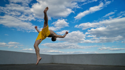 Tricking on street. Martial arts. Man flips back barefoot. Shooted from bottom foreshortening against sky.