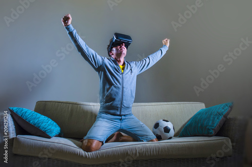 e24d449aba6 young xcited gamer man using VR virtual reality goggles headgear playing  football simulation game celebrating scoring goal at home sofa couch