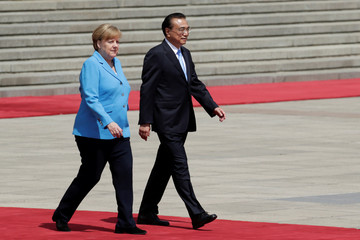 German Chancellor Angela Merkel and Chinese Premier Li Keqiang attend a welcome ceremony outside the Great Hall of the People in Beijing